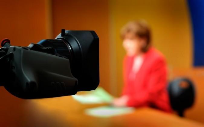 interview télé femme en rouge devant caméra